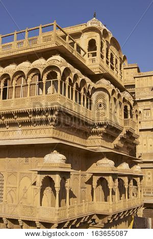 JAISALMER, RAJASTHAN, INDIA - FEBRUARY 18, 2008: Intricately carved walls and balconies of the honey coloured Jaisalmer Palace in Jaisalmer Fort in Rajasthan, India. 17th century Rajput architecture.