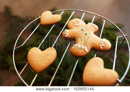 Sweet gingerbread hearts with man on grill. Homemade preparing of pastry for Valentine holiday. Family, love, surprise, pastry concept