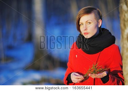 early spring portrait of cute attractive serious young girl with dark hair heat scarf and red jacket looking to camera and standing on wild forest with a sprig in her hands. Outdoor
