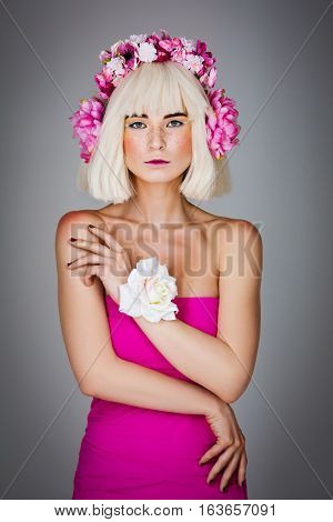 Beautiful young woman in pink dress and blond wig with floral head accessory standing over gray background. Copy space.