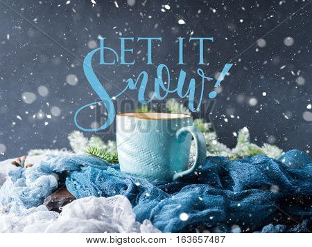 Mug of coffee and milk on dark blue winter background. Hot drink still life with written Let it snow. Snow fall magic