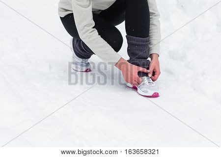 Running in the woods. Beautiful young woman running jogging in the winter forest. Fitness on the street in the winter.
