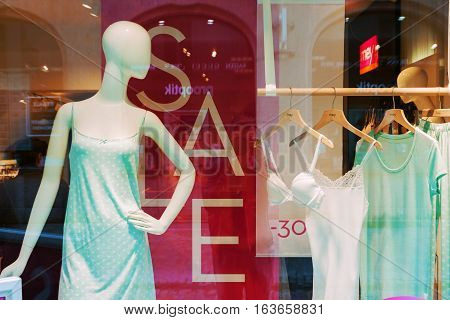 REGENSBURG GERMANY - JULY 14 2016: Shop sale window display with mannequin and hanging clothes in Regensburg Germany
