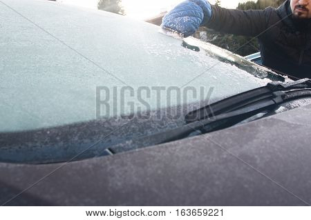 Man is cleaning car windshield from frost and ice.