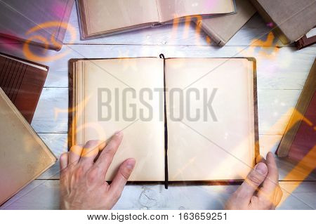 Old magic book with glowing zodiac symbols and man's hand shows important place. Empty page for your text