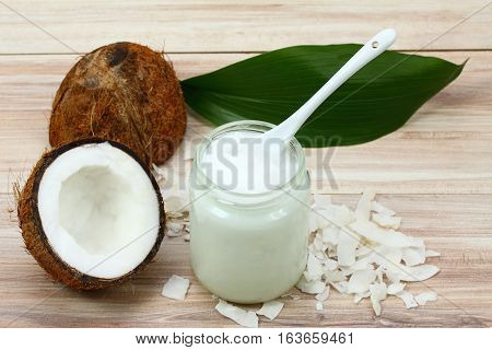 Organic coconut oil from coconuts in a white glass jar fresh coconut cut in half and its pieces