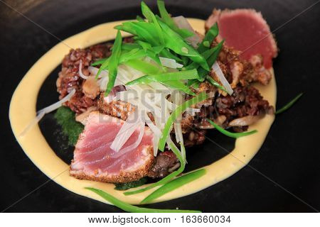 Dinner plate with perfectly seared Ahi fish, vegetables and dressing of spicy cream sauce surrounding all.