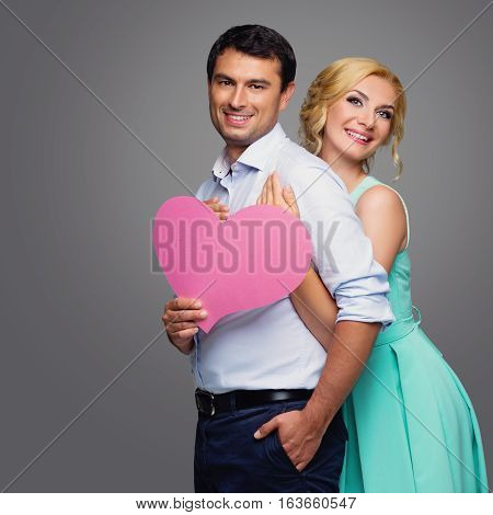 Beautiful young couple holding big pink heart. Blond woman in mint dress and handsome man in shirt and trousers standing on grey background. Valentine's day concept. People in love. Copy space.