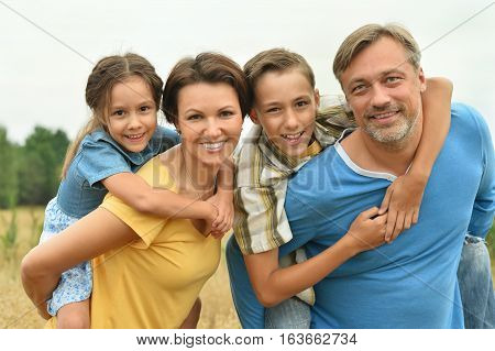Portrait of a happy family at summer field