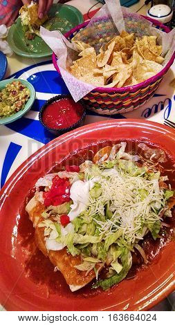 Enchiladas Surpreme served on a bright red plate. Encheladas covered with lettuce tomato cheese and sour cream and surrounded with special sauce. Guacamole and chips and salsa on the side compliment this delicious Mexican cuisine.