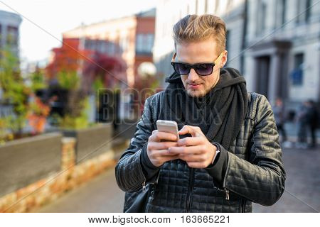 Handsome man using his smartphone and texting