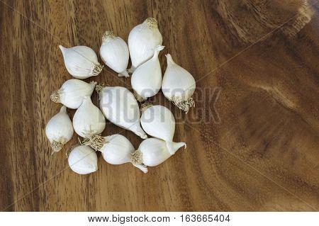 Solo garlic or pearl garlic or single clove garlic on a wooden tray