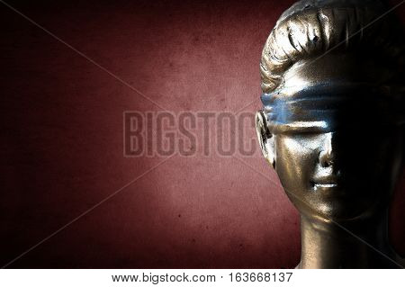 Face of Lady Justice on dark ruddy background