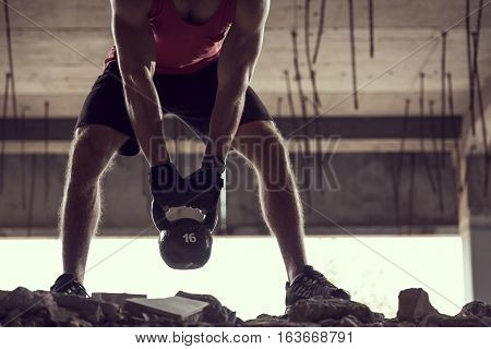 Close up of a young muscular athlete working out lifting a kettlebell weight in an abandoned ruined building
