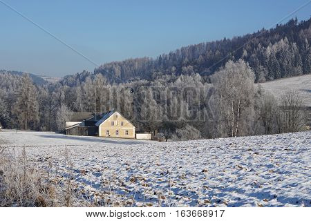 Small countryside house covered by snow in the valley between high mountains placed in Orlicke Hory in the Czech Republic during the winter