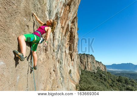 Youth female Rock Climber hanging on vertical Wall expressing Joy and Satisfaction Mountains and Blue Sky Background