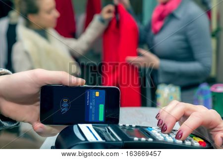 Man completing mobile Payment using modern smart Phone Technology at Store Cashiers Desk with Terminal Salesperson and female Customer interacting on Background