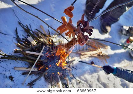 Winter cookout with sausages above the fire placed on snow as a temperature contrast between hot firewood and freezing snow during the December cookout