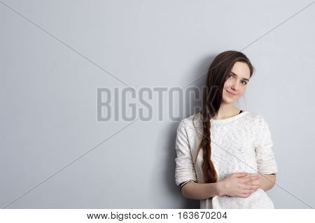 Beautiful girl with a plait hairstyle standing at the gray wall and cute smiles