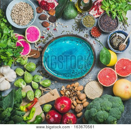 Clean eating concept over grey background with bright blue plate in center, top view, copy space. Vegetables, fruit, seeds, cereals, beans, spices, superfoods, herbs for vegan, gluten free diet