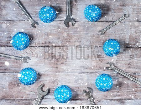 Father's day background on rustic wooden board with wrenches and blue muffin papper cases with stars. Horizontal image. Copy space