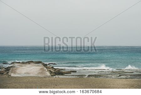 Empty sandy coast and pier at Mediterranean sea in winter day after storm in Alanya, Turkey