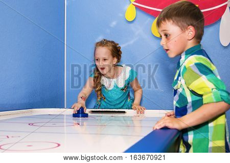 Children intently and enthusiastically plays table hockey.