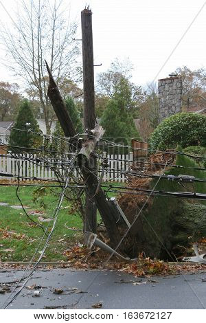 A telephone pole with electric wires breakes in half and falls during super storm sandy on long island