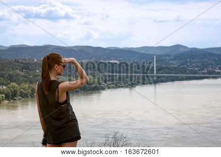 young woman looking far away distance in nature