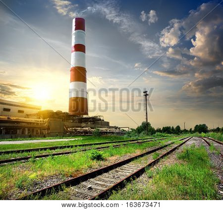 Railroad and industrial tube under cloudy sky