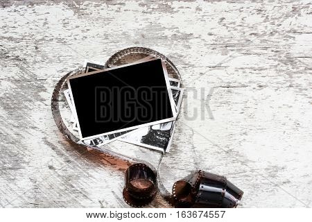 blank photo frame in heart shape made from film negative on white wooden background. love photography concept. valentines day background
