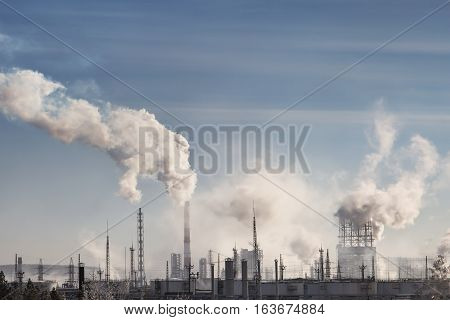 Smoking chimneys at sunset on industrial buildings complex.