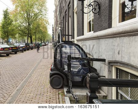 Tiny electric car in amsterdam street. Very small elecric car