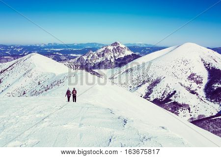 Two tourists on trip in snowy mountains, female tourists on walk European winter mountains, vintage winter mountains with hikers