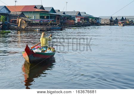 Asia woman selling product while boating on the canel or river in Tonle Sap Cambodia
