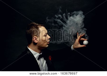 Illusionist man makes smoke his hand on a dark background.