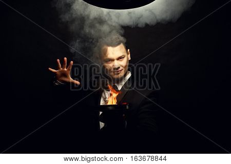 Young brunette magician in costume performing flame tricks