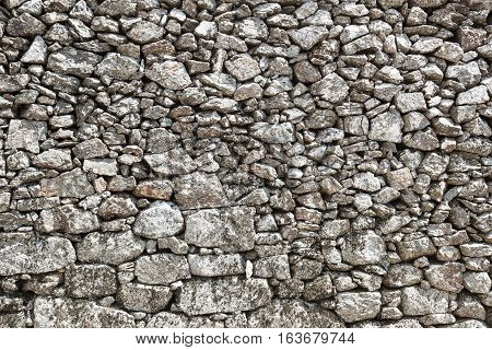 Outdoor stone wall in local stone, retaining wall of stone, background large stone boulders