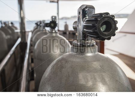 Row of aluminium scuba diving cylinders on dive deck of a luxury liveaboard motor yacht