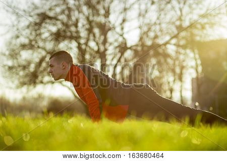Young sportsman working-out in a park, doing a series of pushups