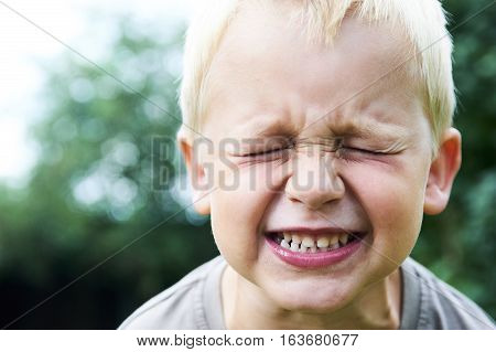 Portrait of a little child blond boy making faces. Outside with natural background.