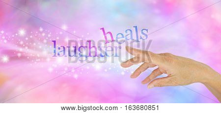 Laughter is the Best Medicine  - Female hand pointing at a sparkly glittering 'LAUGHTER HEALS' on a pink and blue bokeh background