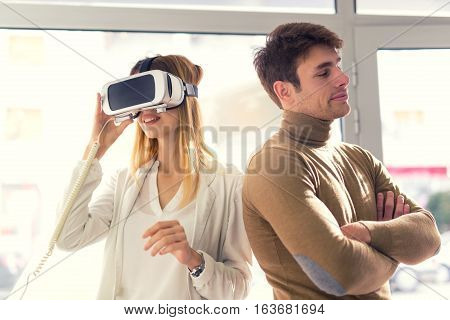 Attractive young woman is holding 3D glasses in the store while a man bored