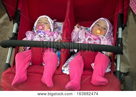 Funny little girls twins in double stroller close up portrait