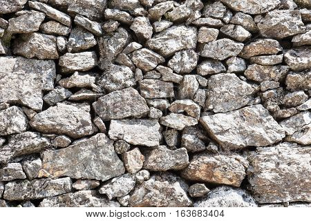 Outdoor stone wall in local stones stone wall of large boulders stone wall background