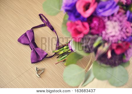 Beautiful Wedding purple Bouquet with brooch and groom bowtie cufflinks on beige chair. Background, floristic composition