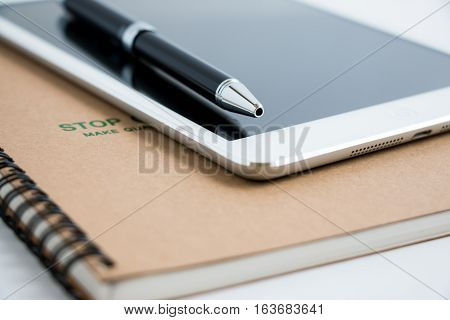 Put A Pen On Tablet And Notebook.