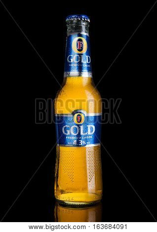 LONDON UK -JANUARY 02 2017: Cold Bottle of Foster's Lager Beer on black background with reflection