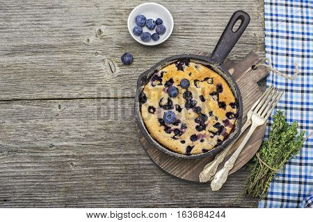 Home comfort food. Fresh blueberry pie in a cast iron frying pan on a wooden background. Top view