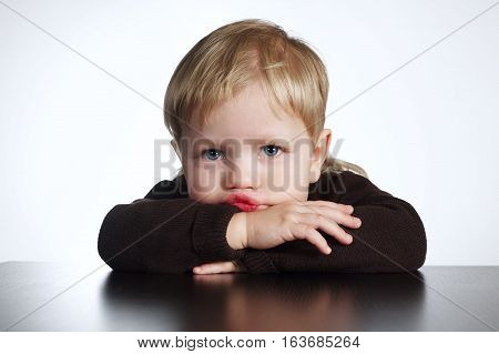 photo of cute little bored boy on white background